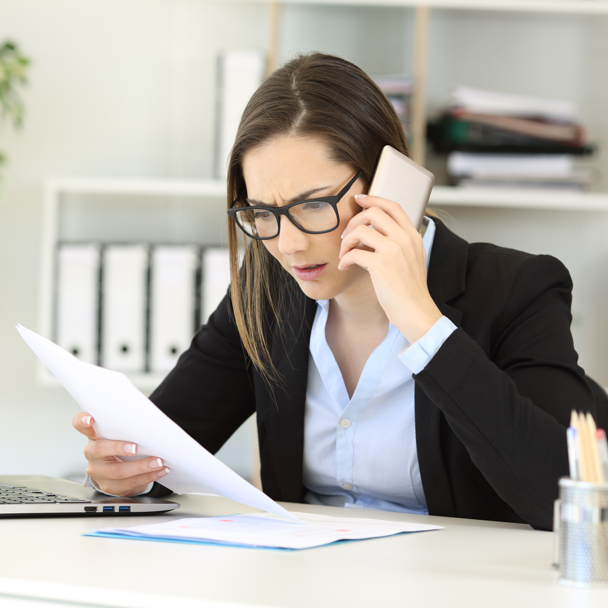 Businesswoman on the phone while reading a report